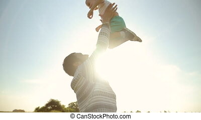 Strong father lobbed son in the sky. Playing with him at sunset in the wheat field
