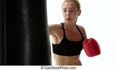 Strong female boxer practicing blows for self defense, dressed in black top visible to the waist, boxing gloves of red color on the hands, close shot white studio, slow motion
