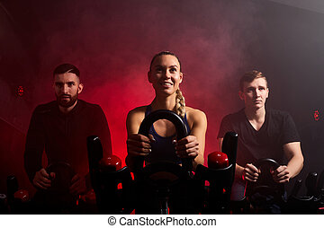 strong female is training with male sportsmen on bike maching in gym