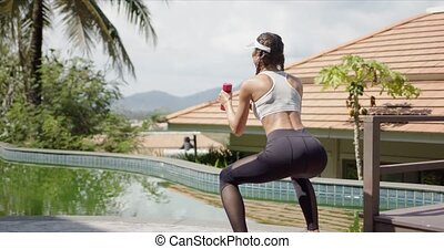 Strong female squatting near swimming pool - Back view of ...