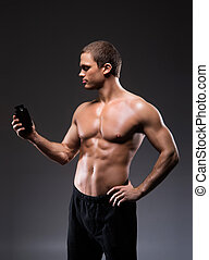 Strong, fit and sporty bodybuilder man with a bottle of sport supplements