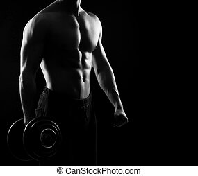 Strong, fit and sporty bodybuilder man with a dumbbell in...