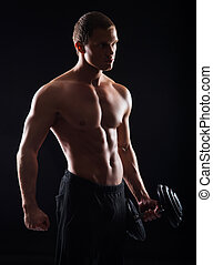 Strong, fit and sporty bodybuilder man with a dumbbell