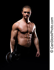 Strong, fit and sporty bodybuilder man with a dumbbell over blac