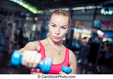 Strong fitness girl with dumbbells. Attractive woman in gym.