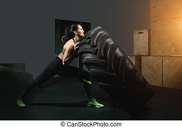 Strong girl flipping a tire in gym.