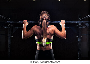 Strong girl in sportswear doing pull up exercise - Strong...