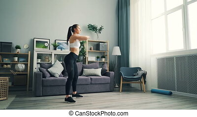 Strong girl student is squatting at home standing on floor...