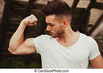 Strong guy with a tattoo on his arm outside