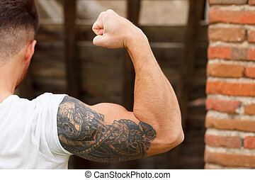 Strong guy with a tattoo on his arm