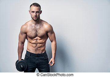 Strong handsome sport man standing with dumbbells looking at...