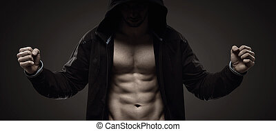 Strong hooded man making muscles