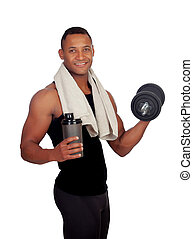 Strong Latin American man with dumbbells drinking protein after