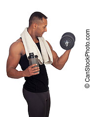 Strong Latin American man with dumbbells drinking protein