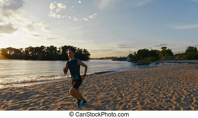 Strong male runner at the beach takes a break to get his...