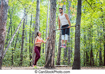 Strong man and athletic woman doing fitness exercise outdoors