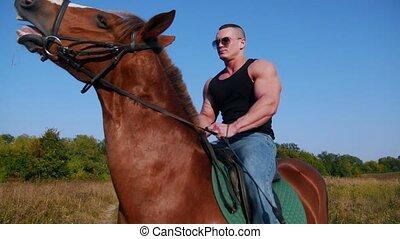 Strong man bodybuilder in a black t-shirt, denim pants,...