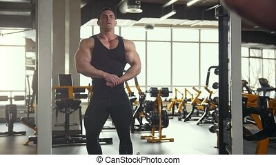 Strong man bodybuilder posing and shows muscles near mirror in the gym