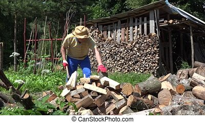 strong man chop wood with axe in village yard. Seasonal...