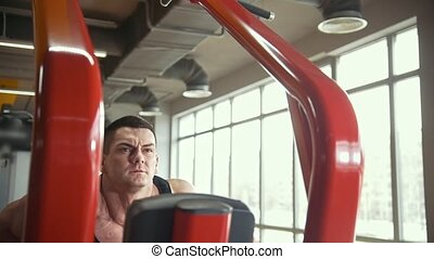 Strong man does exercises in a gym