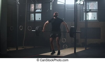 Strong man doing barbell snatch exercise at the gym in slow motion. Male athlete doing barbell snatch exercise in the gym, slow motion