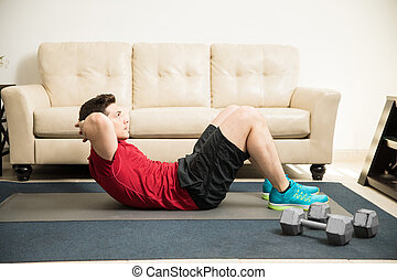 Strong man doing crunches at home