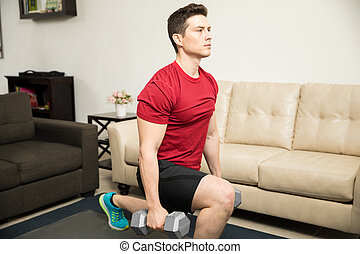 Strong man doing kneeling lunges at home