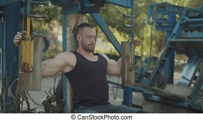 Strong man flexing muscles on chest press machine