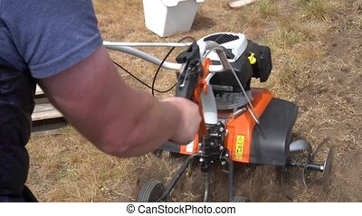 Strong man hands working with petrol cultivator on plowing townhouse yard