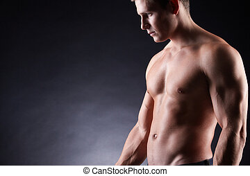 Strong man - Image of shirtless man over dark background