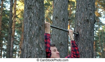 strong man in a plaid shirt pulls himself up on a horizontal bar in the forest.