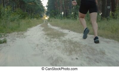 Strong man in active wear doing cardio on sandy road at forest. Focus on muscular legs in sport sneakers. Healthy lifestyle.
