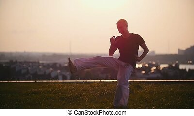 Strong man performs elements of the Brazilian martial art of...