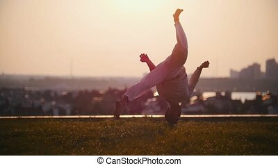 Strong man physically demonstrates very cool tricks on the grass against the background of a pink sunset