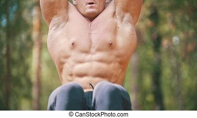 Strong man swinging for abs muscles on the crossbar in...