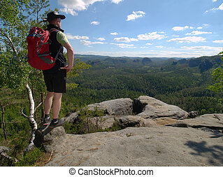 Strong man tourist with a backpack, walks in the mountains
