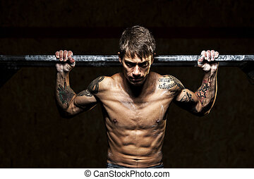 Strong man with naked torso doing pull ups