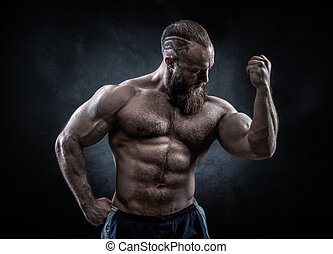 Strong man with perfect abs, shoulders, biceps, triceps and chest