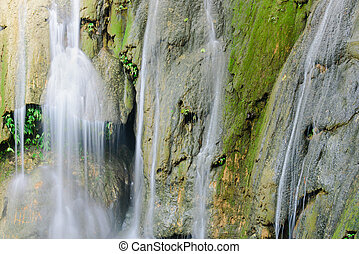 Close-up soft silk stream gushing through cascade tiers limestone rocks. Thac Voi waterfall of tropical rainforest in Thanh Hoa province, Vietnam