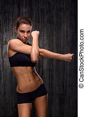 Strong mixed race sporty woman demonstrating biceps