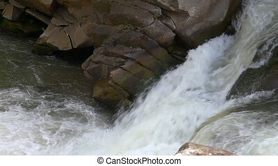 Strong mountain stream flowing over rocks
