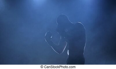 Strong muscular body of a boxer in silhouette and slow motion