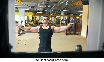 Strong muscular man at weight training in a gym