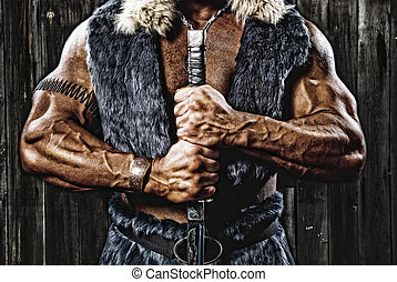 Strong muscular man defender warrior with sword in hand on...
