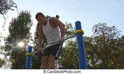 Strong muscular man doing muscle ups in a park. Young athlete doing chin-ups on horizontal bars outdoor. Fitness muscular man training outside in summer. Sportsman pulling up. Workout sport lifestyle