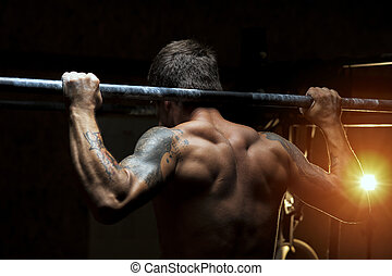 Strong muscular man doing pull up exercise in gym