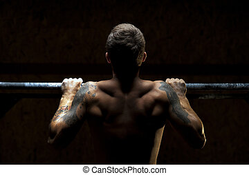 Strong muscular man doing pull up exercise on bar
