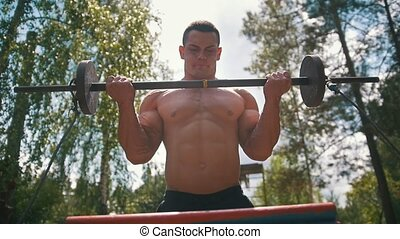 Strong muscular man engaged with old heavy iron crossbar outdoors at summer forest
