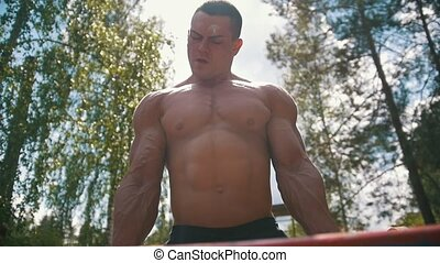 Strong muscular man engaged with old heavy iron crossbar outdoors