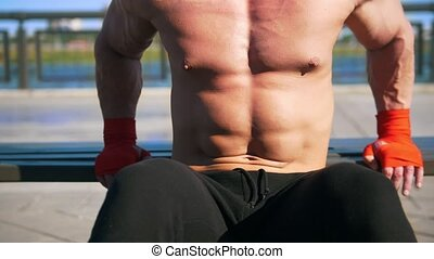 Strong muscular man have power training outdoor - push-UPS from the athletic bench
